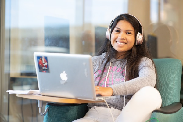 Young girl with headphones on smiling while using a laptop