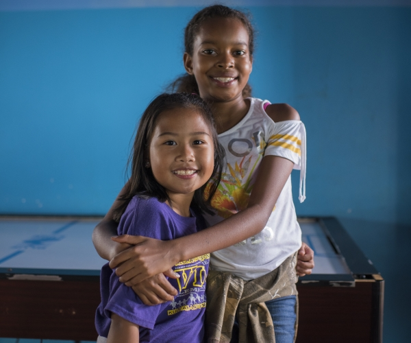 Two young girls smiling and hugging